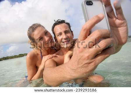 Couple making selfie in the sea with waterproof smartphone - stock photo