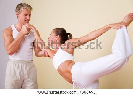 Couple (male / female) doing yoga exercises together - stock photo
