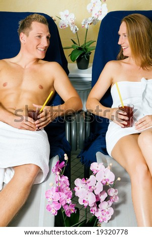 Couple male / female relaxing on beds in a health club drinking juice - stock photo