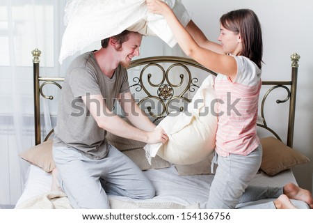 couple, man and woman fighting together with pillows in bed  - stock photo
