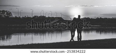Couple Man and Woman Hugging in Love staying on Beach seaside with Sunset, edited in black and white - stock photo