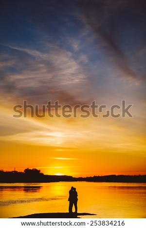 Couple Man and Woman Hugging in Love staying on Beach seaside with Sunset, vertical image - stock photo