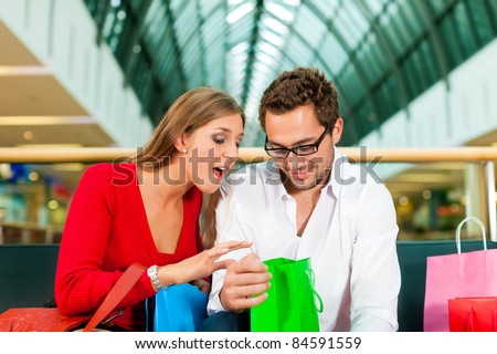 Couple - man and woman - in a shopping mall with colorful bags, they are checking what exactly they do have bought, she is surprised