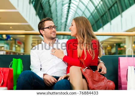 Couple - man and woman - in a shopping mall with colorful bags; they having a break