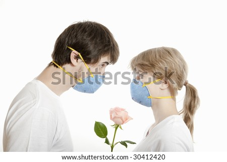 Couple, man and woman in masks  face to face looking over rose flower ,  against white background - stock photo