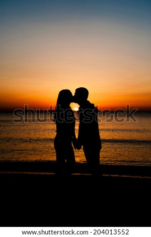 Couple Man and Woman kissing in Love staying on Beach seaside with Sunset scenery People Romantic relationship and Friendship concept - stock photo