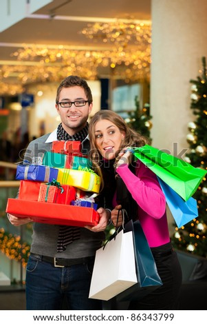 Couple - man and woman - with Christmas presents, gifts and shopping bags - in a mall in front of a Christmas tree