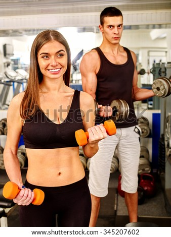 Couple man and woman  working with  dumbbells his body at gym.  - stock photo
