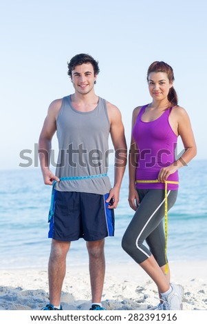 Couple measuring their waist at the beach - stock photo