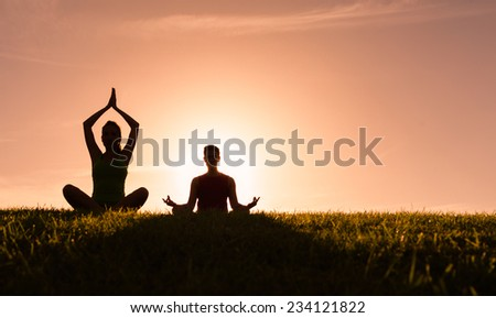 Couple meditating in a yoga pose outdoors - stock photo