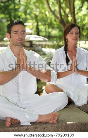 Couple meditating in stone garden - stock photo