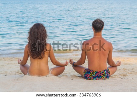 Couple meditating on beach in lotus position