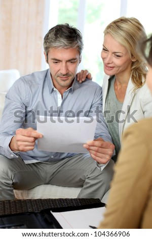 Couple meeting advisor at home - stock photo