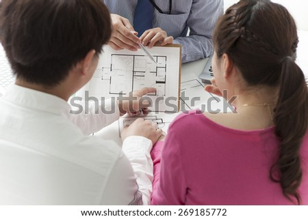 Couple meeting architect for plans of future home - stock photo