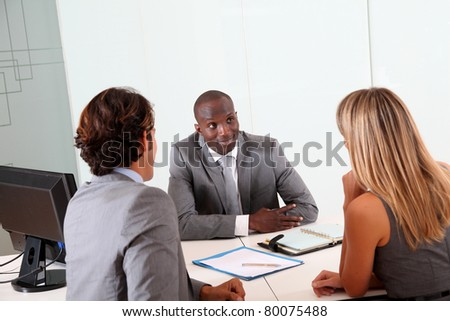 Couple meeting businessman in office - stock photo
