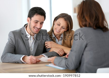 Couple meeting financial adviser for construction project - stock photo