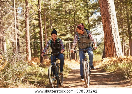 Couple mountain biking through forest, close up - stock photo