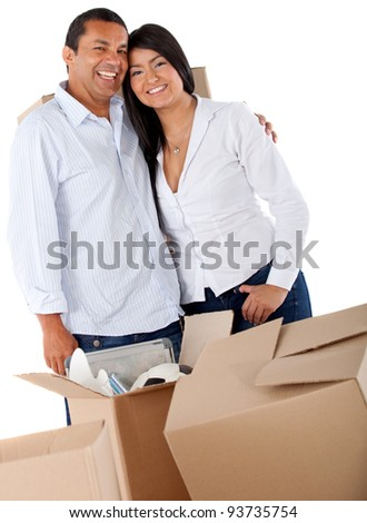 Couple moving house and packing in boxes - stock photo