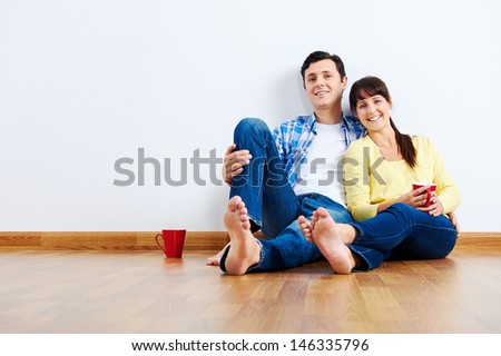 couple moving in to new home, empty floor - stock photo