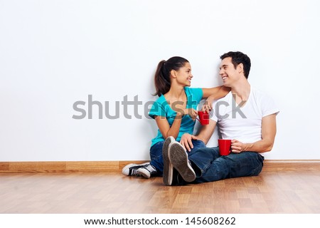 couple moving into empty new home sitting on floor together and drinking coffee - stock photo