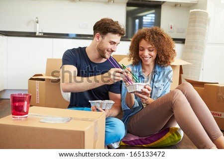 Couple Moving Into New Home Enjoying Takeaway Meal - stock photo