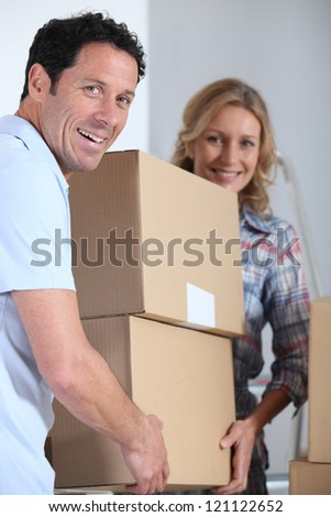 Couple moving pile of boxes - stock photo