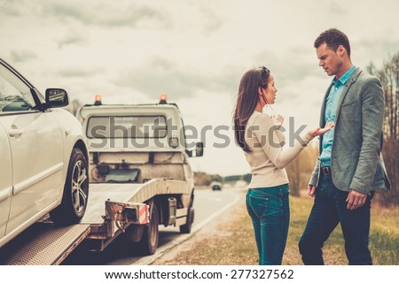 Couple near tow-truck picking up broken car  - stock photo