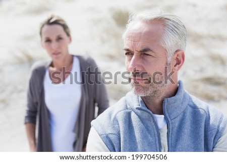 Couple not talking after argument on the beach on a bright but cool day - stock photo