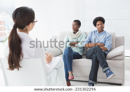 Couple not talking to each other in therapists office - stock photo
