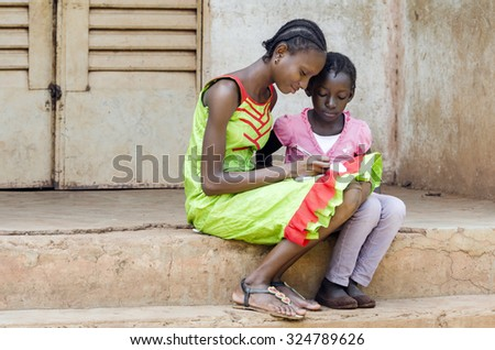 Couple of African Schoolgirls Learning Repeating their lessons outside of a classroom. Older girl showing younger child how to do their homework. Africa Education Symbol. - stock photo