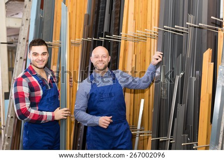 Couple of american workmen inspecting window frames at factory - stock photo