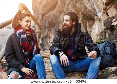 Couple of backpackers resting while out hiking in mountains, couple of hipster guys smiling while having conversation, adventure trip in mountains, hike tour in mountain landscape, flare sun - stock photo