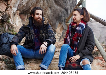 Couple of backpackers resting while out hiking in mountains, couple of hipster guys taking break sitting on the rocks, adventure trip in mountains, hike tour in mountain landscape, flare sun - stock photo