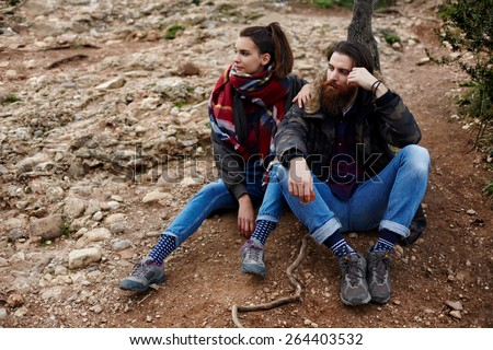 Couple of backpackers resting while out hiking in mountains, couple of hipster guys taking break sitting on the rocks, adventure trip long way in mountains, hike tour in mountain landscape - stock photo