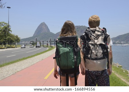 Couple of backpakers walking through Rio de Janeiro with Sugar Loaf in the background. - stock photo
