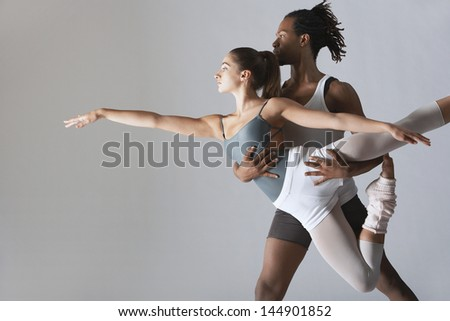 Couple of ballet dancers posing over gray background - stock photo