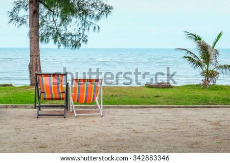 Couple of beach chairs on sea coast at thailand. - stock photo