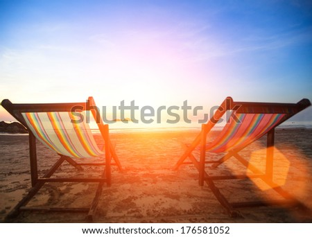 Couple of beach chairs on the evening sea coast. - stock photo