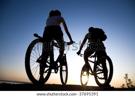 Couple of bicyclists on the brink of a rock looks at a sunset