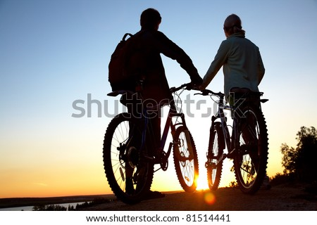 Couple of bicyclists on the brink of  rock looks at  sunset - stock photo