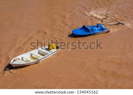 Couple of boats dragged by the water in a flood. - stock photo