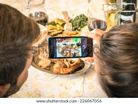 Couple of boyfriend and girlfriend taking a food selfie in dinner restaurant - Moda of catching the instant with modern smartphone at lunch meeting with typical italian food - stock photo