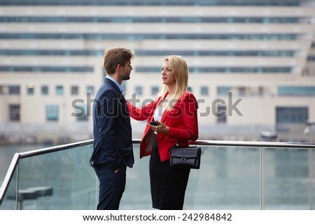 Couple of business colleagues at meeting talking about some projects, business people discussing future architecture project outdoors, real state agent talking with agent realtor - stock photo