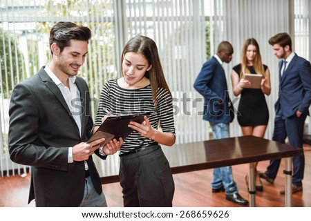 Couple of business people planning with a multi-ethnic group in the background in a office. - stock photo