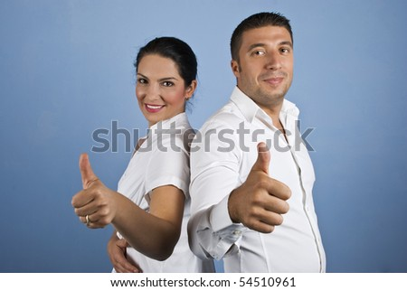 Couple of  business people ,woman and man dressed in white shirts giving thumbs up on blue background