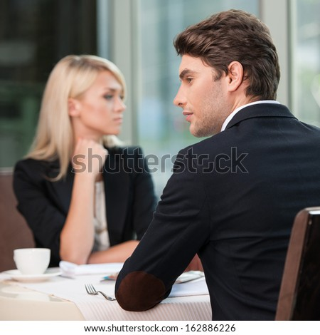 Couple of businesspeople looking in different sides. Disagreement and misunderstanding in communication.  - stock photo