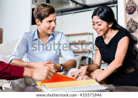 Couple of Caucasian man and Asian woman and shop assistant in furniture store planning furnishing of home together - stock photo