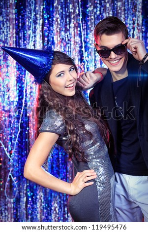 Couple of cheerful young people having a rest at a party. - stock photo