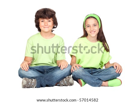 Couple of children with same clothes sitting isolated on white background - stock photo