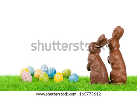 Couple of chocolate easter bunnies with colorful eggs on a meadow. - stock photo